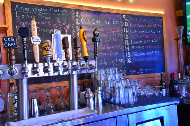 Some of the 16 taps and beer menu board behind them.